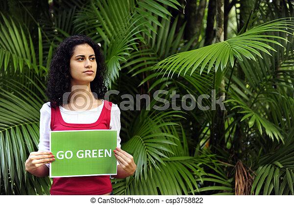 Conservación de Medio Ambiente: mujer en el bosque sosteniendo una señal verde - csp3758822