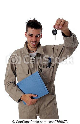 Un mecánico amistoso sosteniendo las llaves del coche - csp9769673