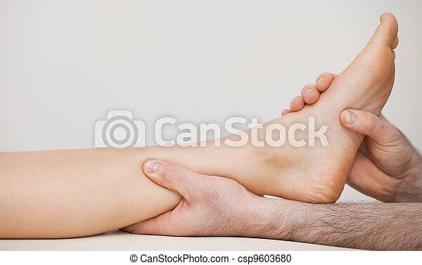 Chiropodista sosteniendo el tobillo de un paciente - csp9603680