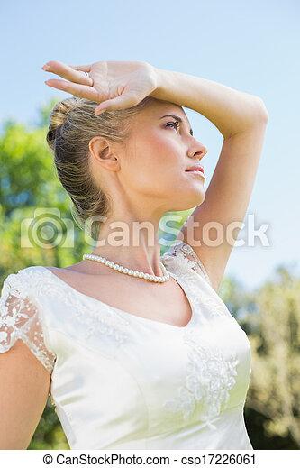 Linda novia rubia sosteniendo el brazo a la frente en un día soleado - csp17226061