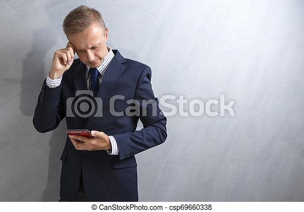 Hombre de traje azul pensando. Sosteniendo el móvil rojo en las manos. Contra la pared gris grunge. - csp69660338