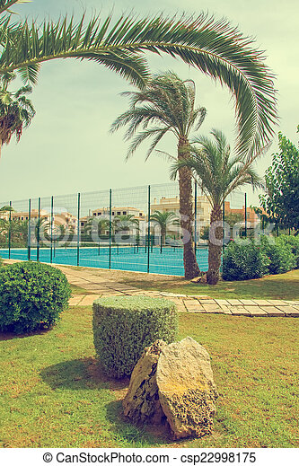 Tennis courts in the park with palm trees. - csp22998175