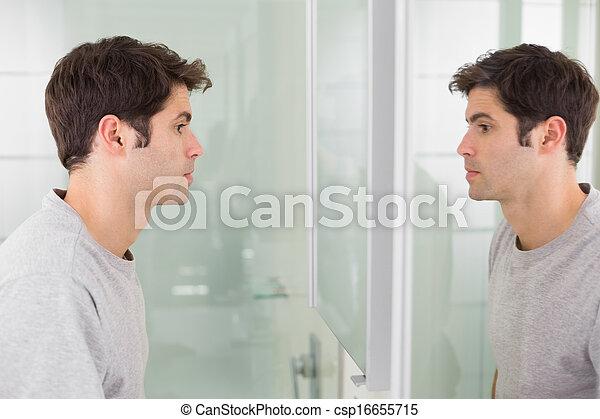 tensed man looking at self in bathroom mirror side view of a tensed
