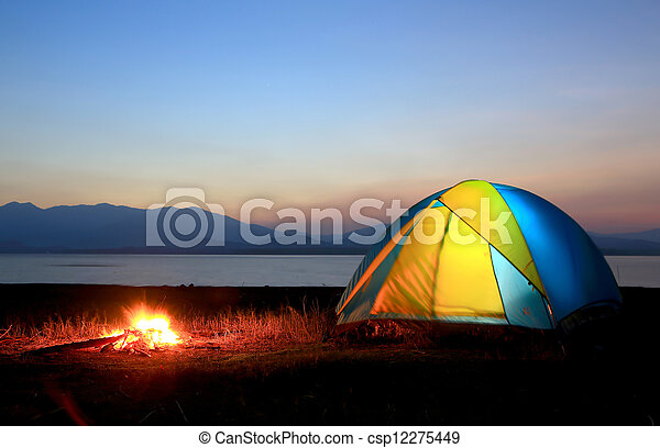 tent and campfire at sunset,beside the lake - csp12275449