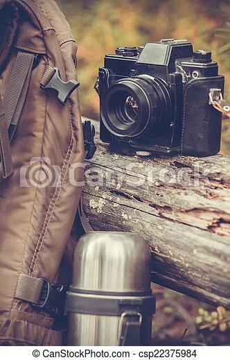Estilo de vida de excursión equipo de camping retro cámara de cámara de fotos y termos naturaleza al aire libre en el fondo - csp22375984