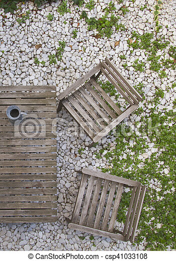Terrace Table And Chairs From Grey Wood On The Stones And Grass