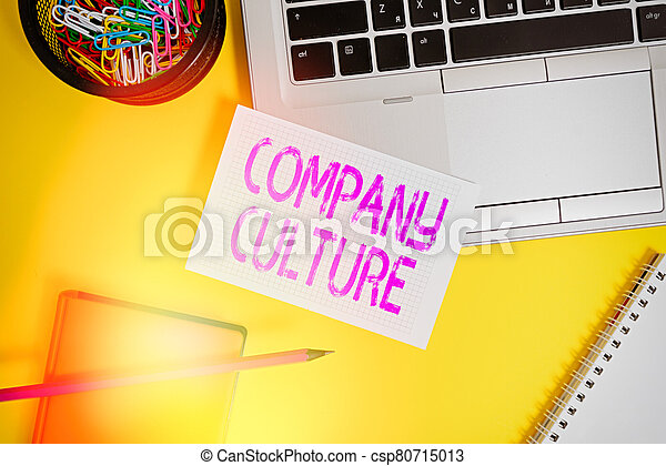 Text sign showing Company Culture. Conceptual photo The environment and elements in which employees work Laptop pencil sheet clips container spiral notebook colored background. - csp80715013