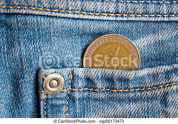 Thai coin with a denomination of 10 baht in the pocket of light blue denim jeans - csp56173473