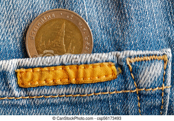 Thai coin with a denomination of 10 baht in the pocket of old biege denim jeans - csp56173493