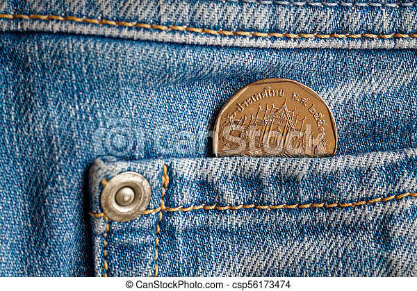 Thai coin with a denomination of 5 baht in the pocket of light blue denim jeans - csp56173474