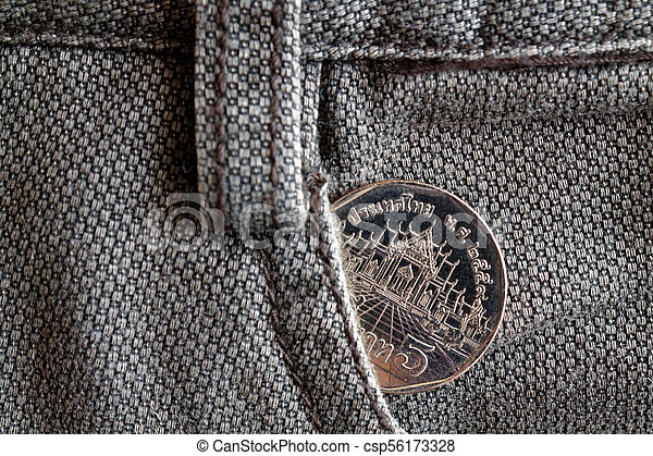 Thai coin with a denomination of 5 baht in the pocket of old brown denim jeans - csp56173328