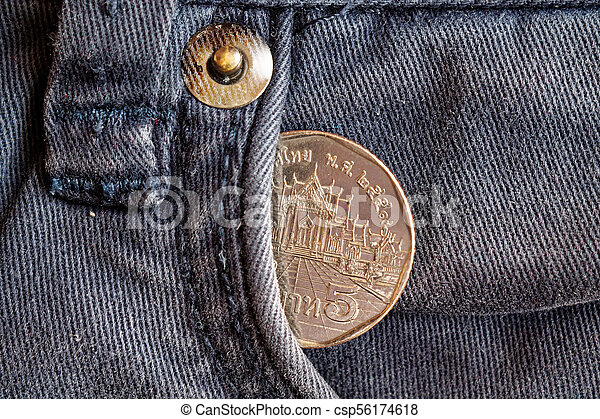 Thai coin with a denomination of five baht in the pocket of obsolete blue denim jeans - csp56174618