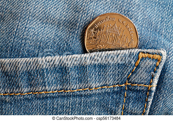 Thai coin with a denomination of five baht in the pocket of old blue worn denim jeans - csp56173484