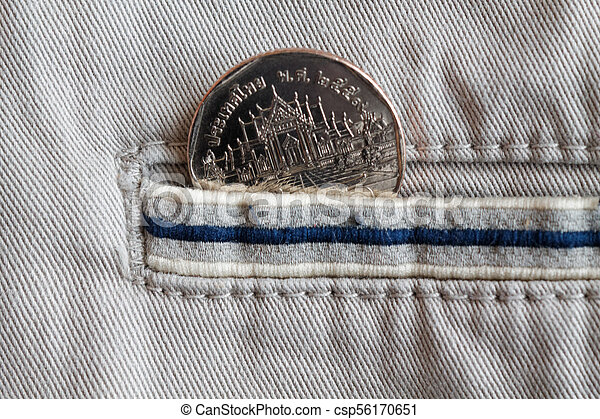 Thai coin with a denomination of five baht in the pocket of beige denim jeans with blue stripe - csp56170651