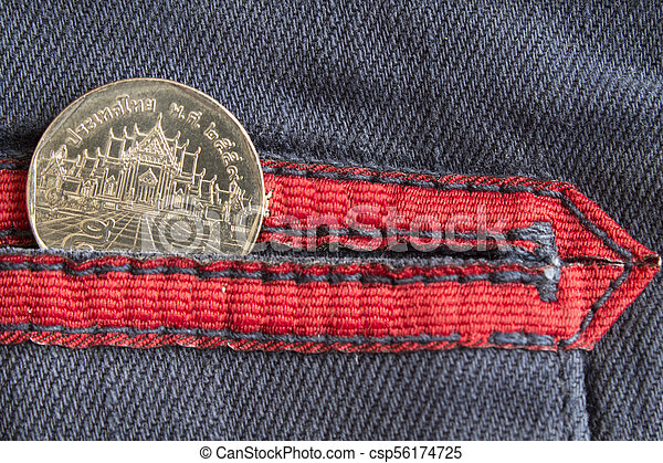Thai coin with a denomination of five baht in the pocket of worn blue denim jeans with red stripe - csp56174725