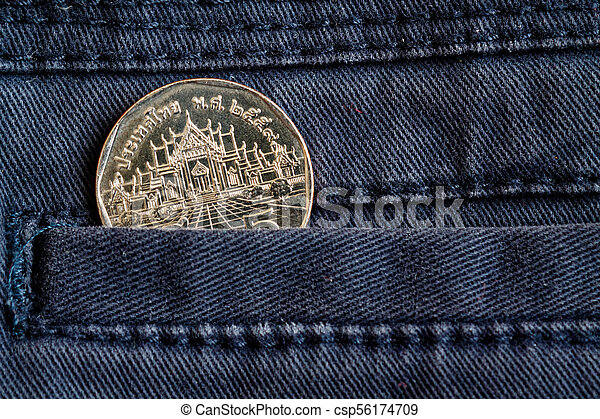 Thai coin with a denomination of five baht in the pocket of dark blue denim jeans - csp56174709