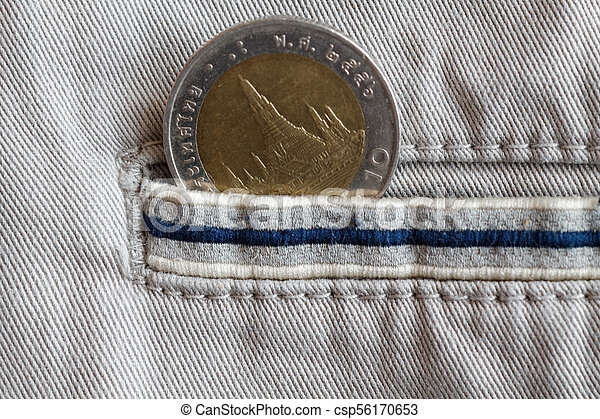 Thai coin with a denomination of ten baht in the pocket of beige denim jeans with blue stripe - csp56170653