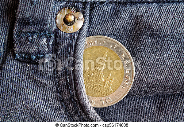 Thai coin with a denomination of ten baht in the pocket of obsolete blue denim jeans - csp56174608