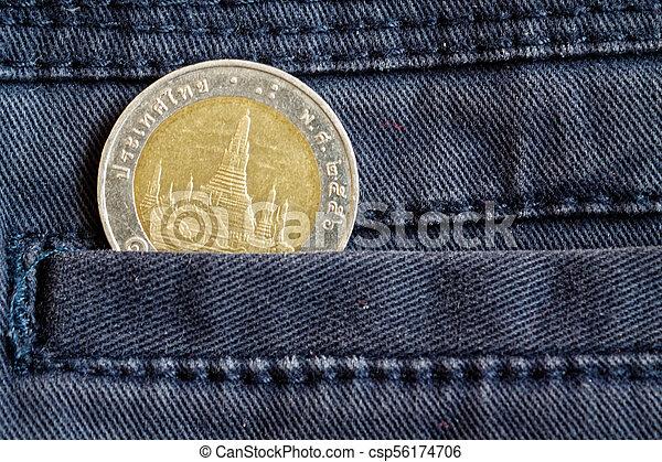 Thai coin with a denomination of ten baht in the pocket of dark blue denim jeans - csp56174706