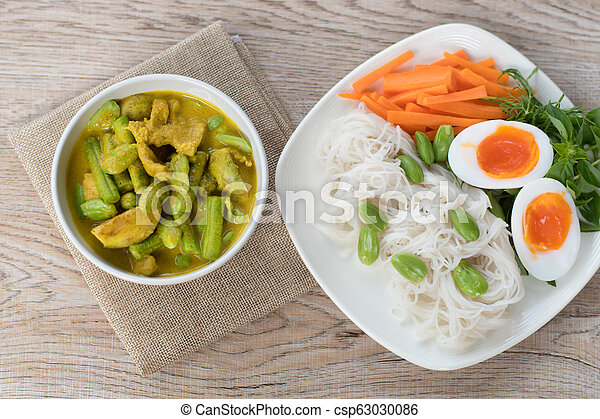 Thai food spicy pork and vegetable Parkia speciosa curry in coconut milk and Thai rice flour noodles - csp63030086