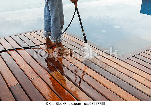 Thai man do a pressure washing on timber - csp23627788