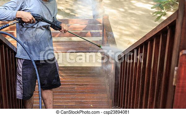 Thai man do a pressure washing on timber - csp23894081