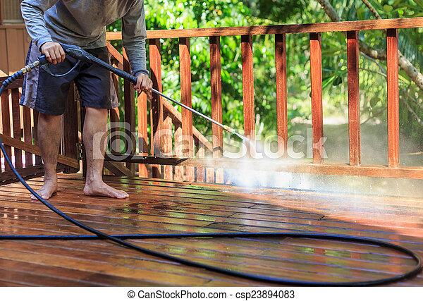Thai man do a pressure washing on timber - csp23894083