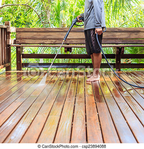 Thai man do a pressure washing on timber - csp23894088