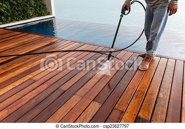 Thai man do a pressure washing on timber - csp23627797