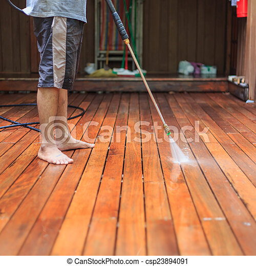 Thai man do a pressure washing on timber - csp23894091