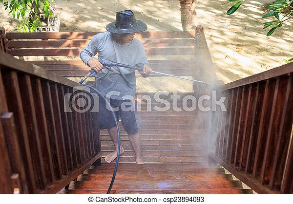 Thai man do a pressure washing on timber - csp23894093