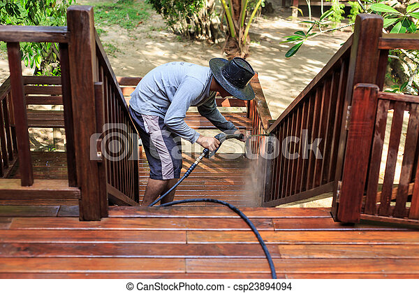 Thai man do a pressure washing on timber - csp23894094