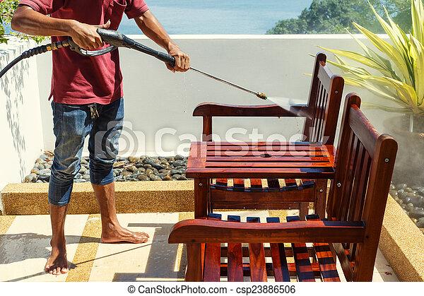 Thai man do a pressure washing on timber - csp23886506