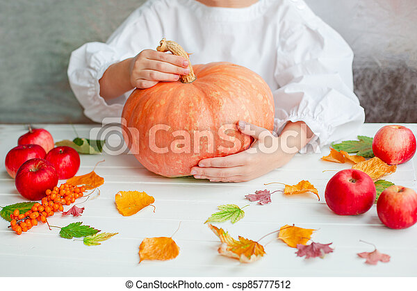 Thanksgiving concept. Hands holding pumpkin and apples, flowers, autumn leaves on a rustic table, flat lay. - csp85777512