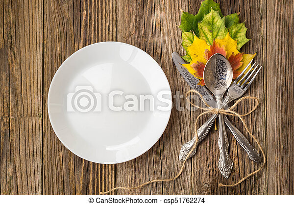 Thanksgiving Dinner Plate With Fork Knife And Autumn Leaves On Rustic Wooden Table Background Top Stock Photo