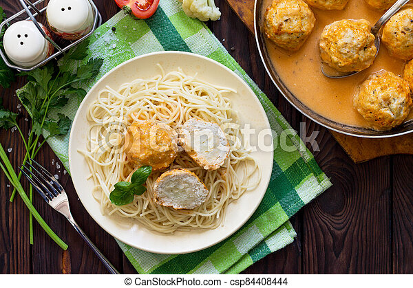 Thanksgiving Turkey dinner. Meat balls turkey with cauliflower in tomato sauce and spaghetti on a wooden table. Copy space, top view flat lay background. - csp84408444
