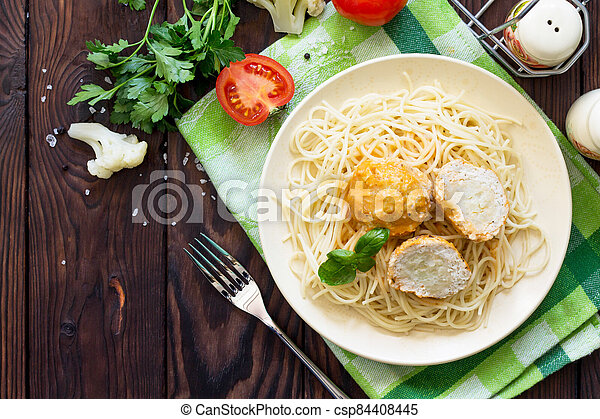 Thanksgiving Turkey dinner. Meat balls turkey with cauliflower in tomato sauce and spaghetti on a wooden table. Copy space, top view flat lay background. - csp84408445