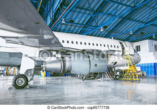 The aircraft is in the aviation hangar. Theme repair and maintenance of airplane airlines. - csp65777736