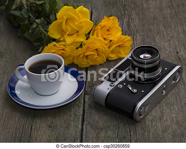 the ancient film camera, bouquet and coffee on an old wooden table, a still life - csp30260859