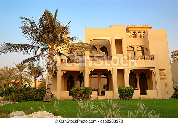 The Arabic style villa and palm during sunset at luxury hotel, Dubai, UAE - csp8283378