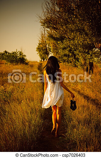 The barefoot girl in white dress with shoes in hand is on the field. Rear view - csp7026403