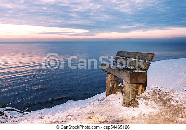 The beautiful winter night at sea stands a lonely bench - csp54465126