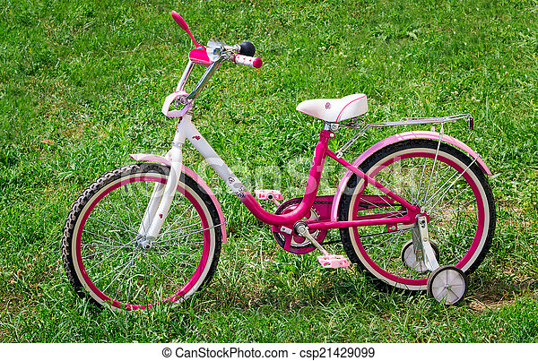 The bicycle for the girl on a green lawn. - csp21429099