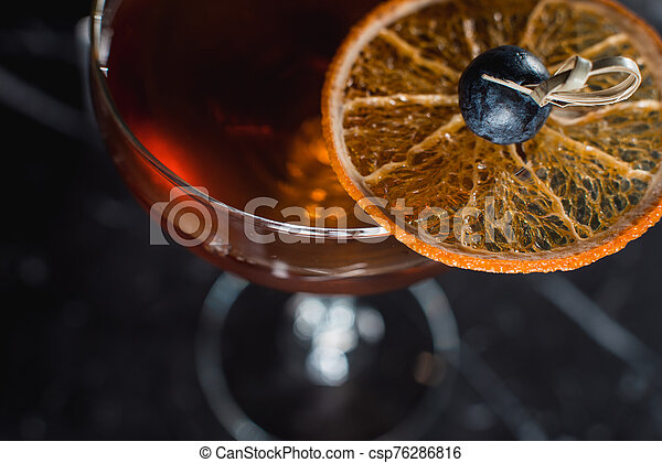 The Boulevardier Cocktail with orange chips on top. On a bar desk - csp76286816
