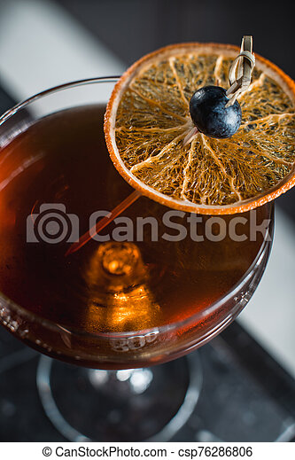 The Boulevardier Cocktail with orange chips on top. On a bar desk - csp76286806