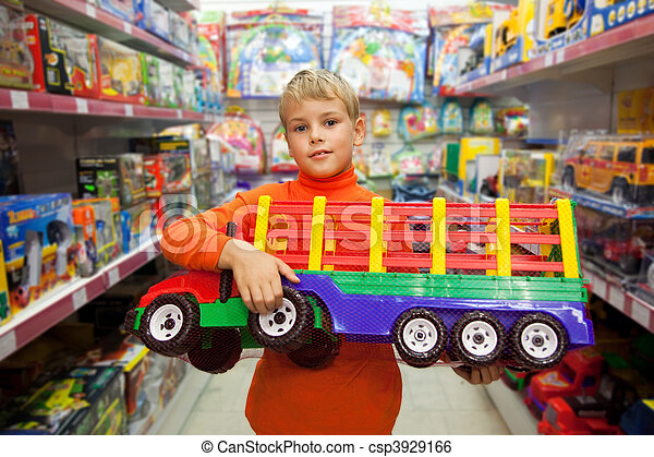 The boy in shop with the big model of the truck in hands - csp3929166