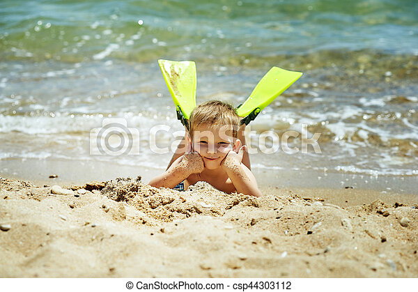 the boy on the beach with a snorkel and fins - csp44303112