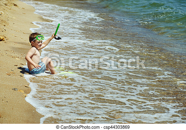 the boy on the beach with a snorkel and fins - csp44303869