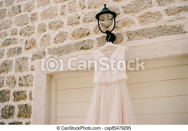 The bride's dress on the background of a stone wall on a black street lamp. - csp85479295