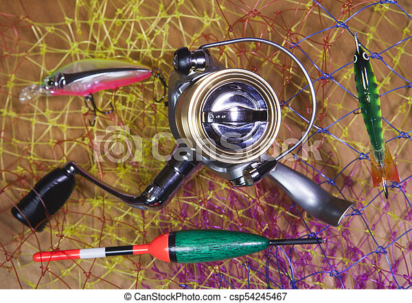 The coil, float and baits on a fishing net background. - csp54245467